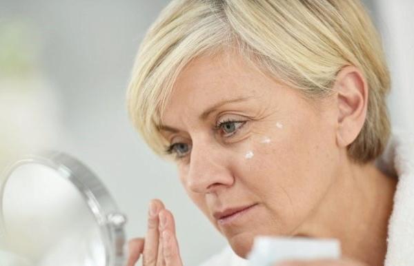 zhenschina s kremom u zerkala
